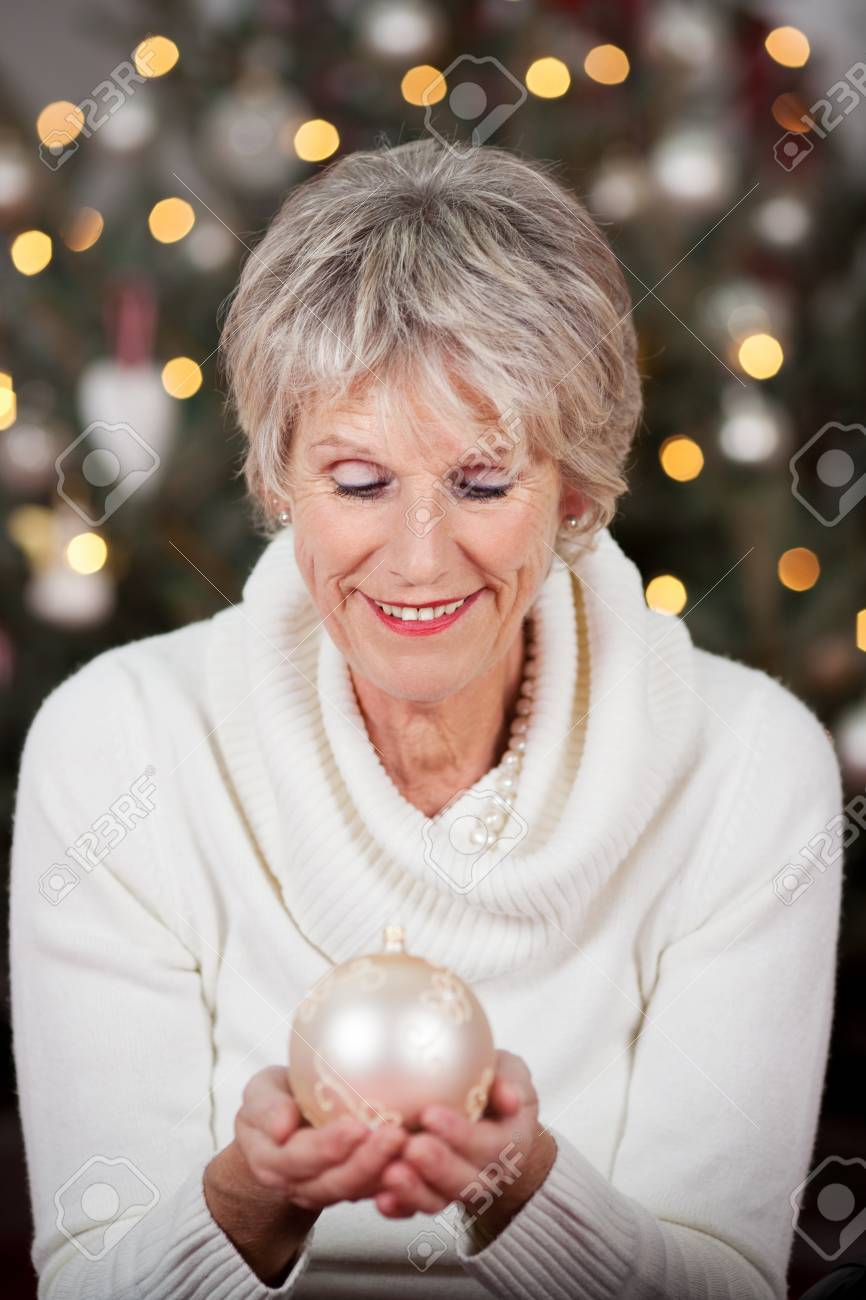 Stylish senior lady with a beautiful smile holding a white Christmas bauble cupped in her hands in front of a sparkling Christmas tree Stock Photo - 20771805