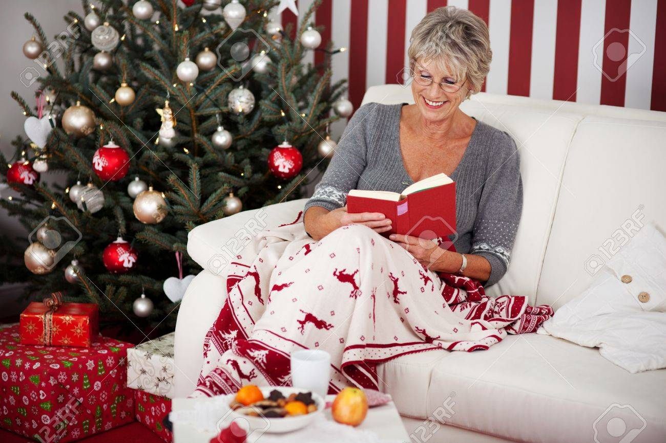 Elderly attractive woman relaxing under a colourful blanket with reindeer on the sofa reading a book in front of the Christmas tree Stock Photo - 20785963