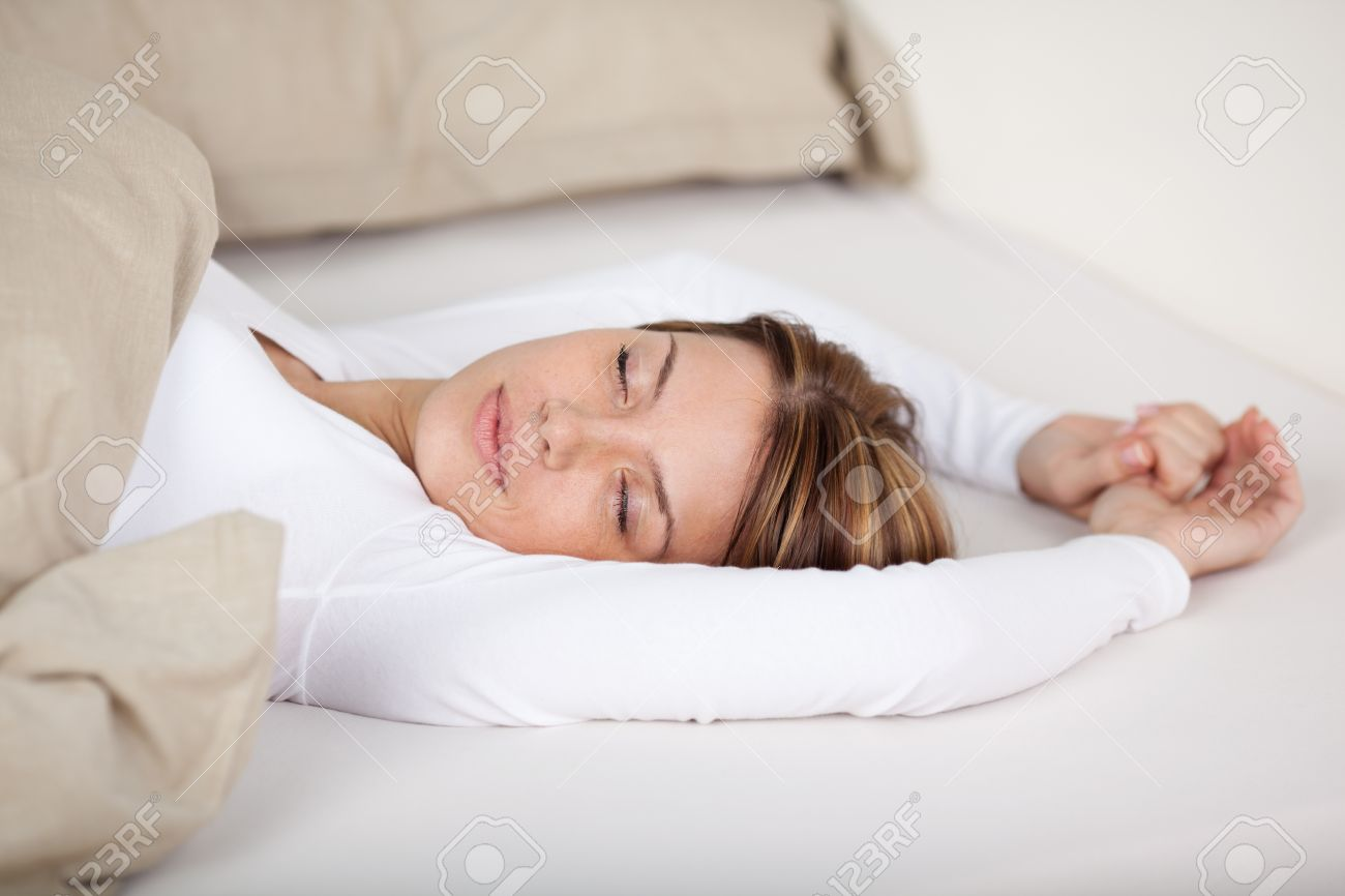 Serene Woman Relaxing In Bed Lying With Her Eyes Closed And Arms Stock Photo Picture And Royalty Free Image Image 21110716