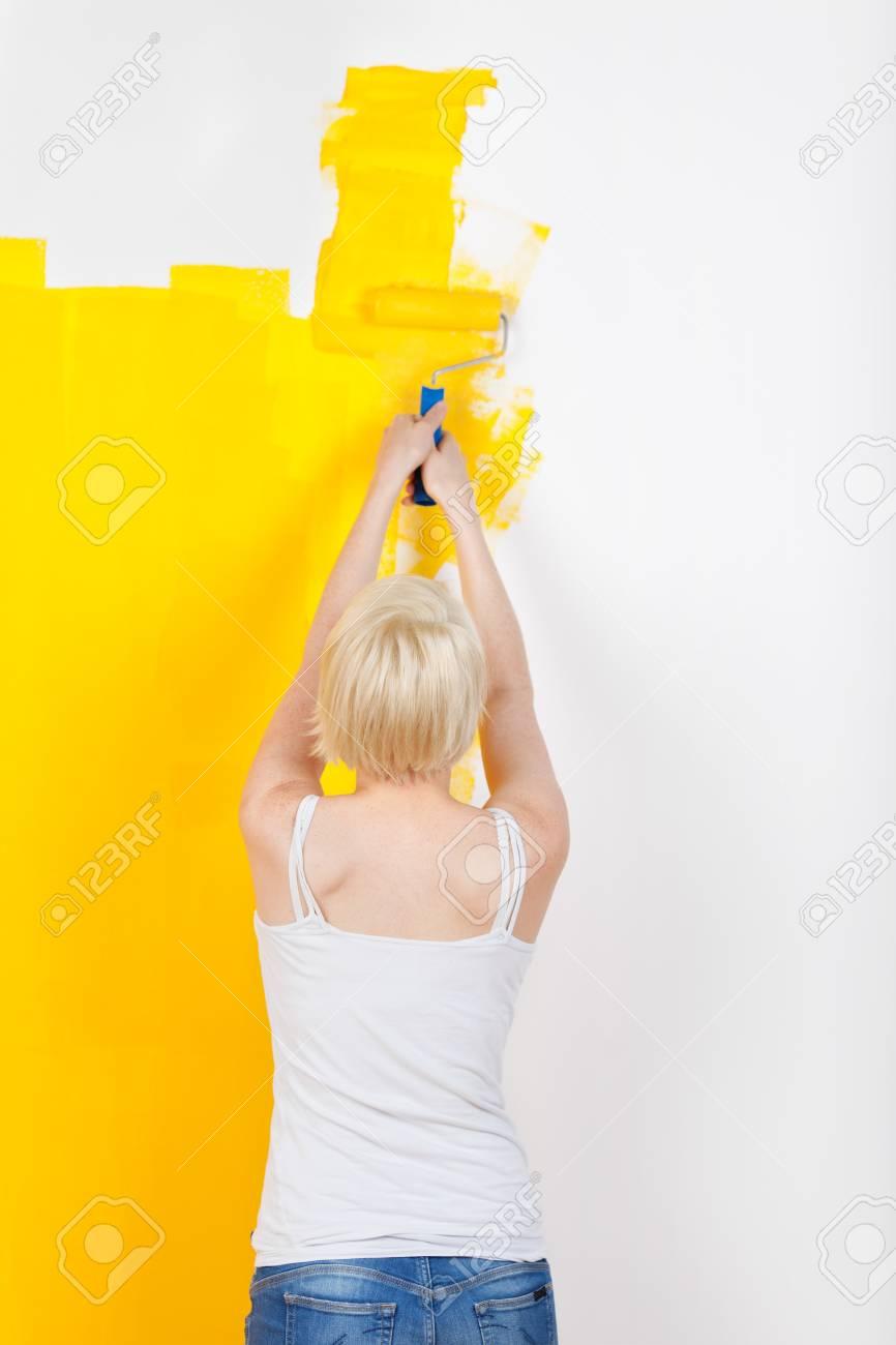 Vue Arrière D Une Jeune Femme Blonde Peindre Le Mur Jaune