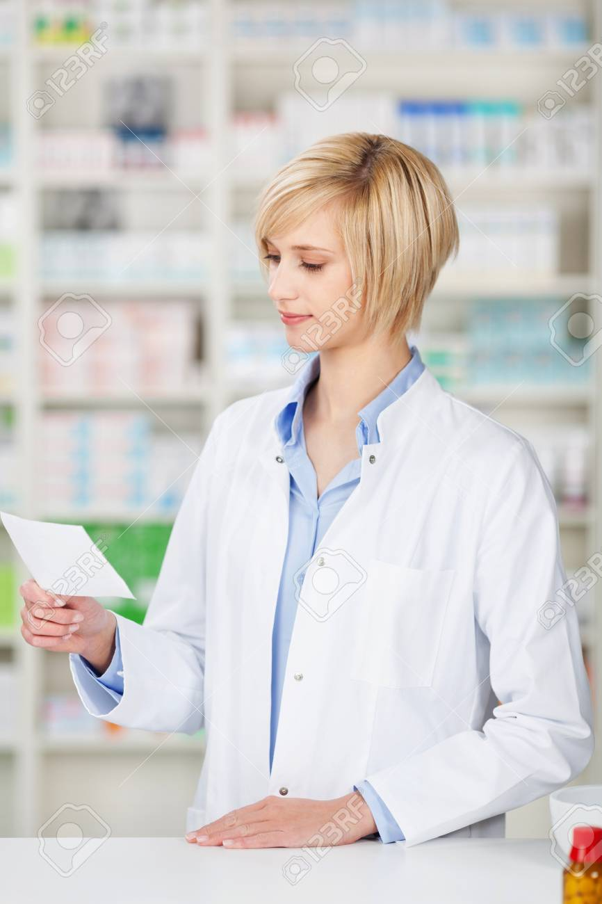 female pharmacist looking at prescription at the counter Stock Photo - 21112234