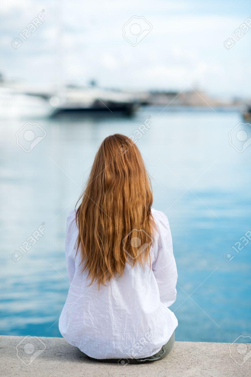 Mujer Sentada En El Puerto En El Muelle De Espaldas A La Cámara