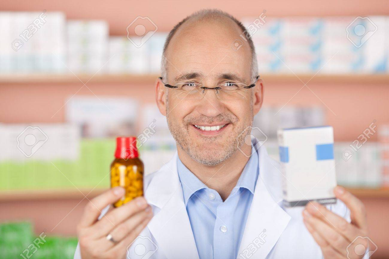Happy pharmacist showing different medicines at the pharmacy Stock Photo - 21170585