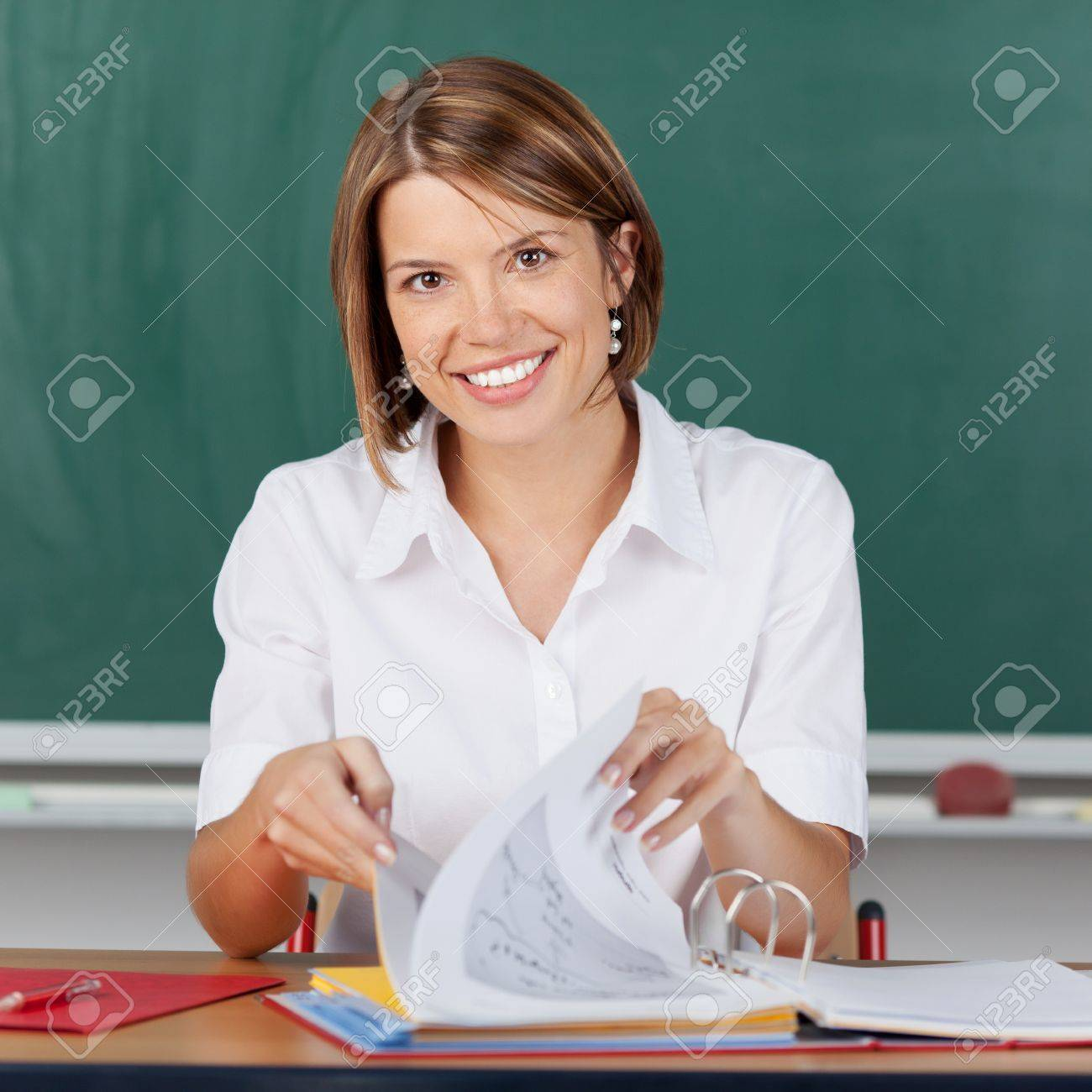 Smiling teacher checking her notes for class paging through pages in a large file while sitting in front of a blackboard Stock Photo - 21148083