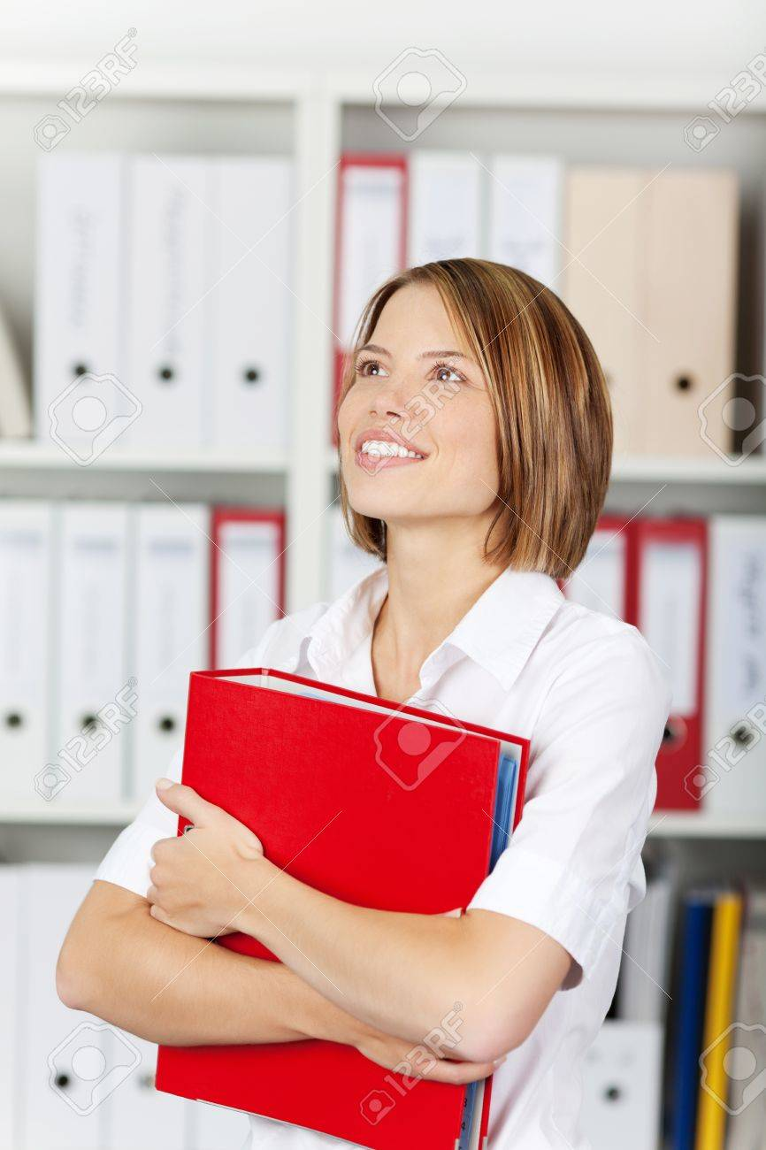 Smiling businesswoman or office worker wearing a bright white blouse holding a red binder Stock Photo - 21148502