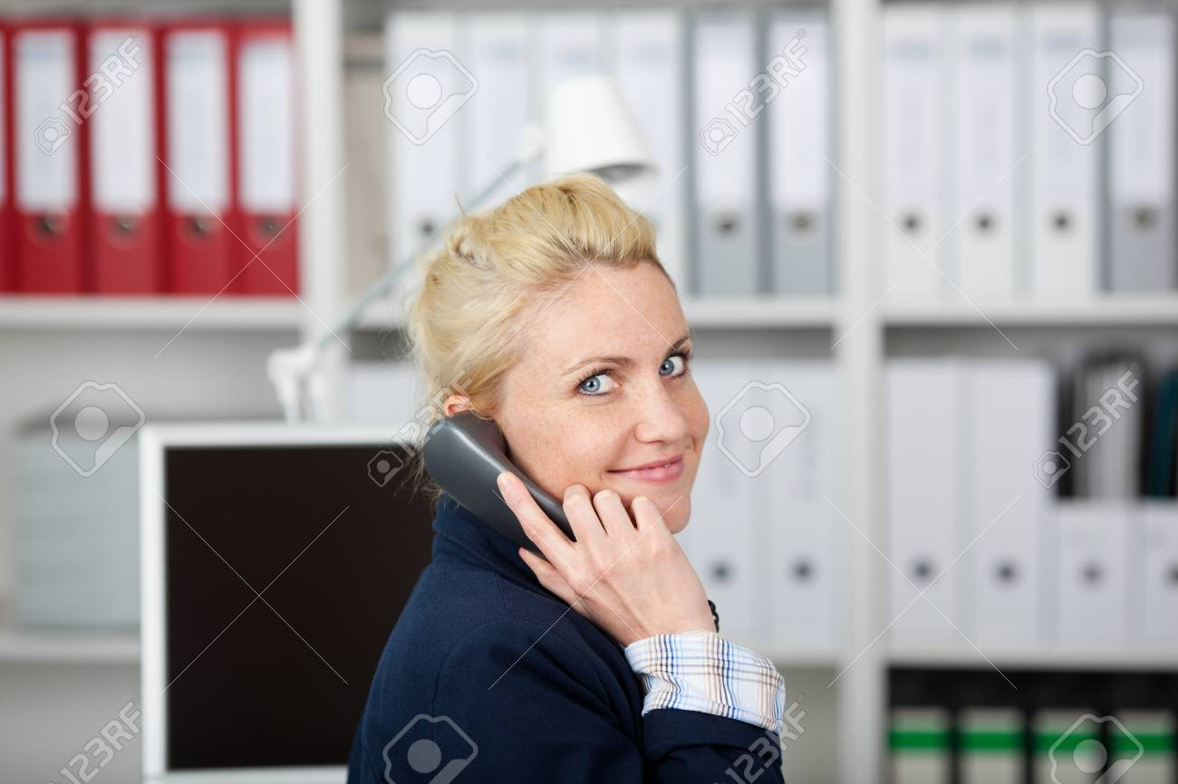 Portrait of a young smiling businesswoman using telephone in the office Stock Photo - 21149385