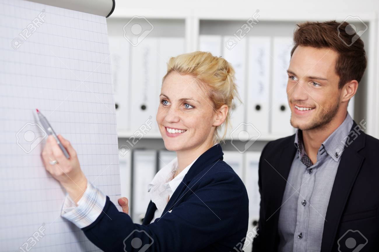 Side view of two young businesspeople working on flipchart at office Stock Photo - 21149569