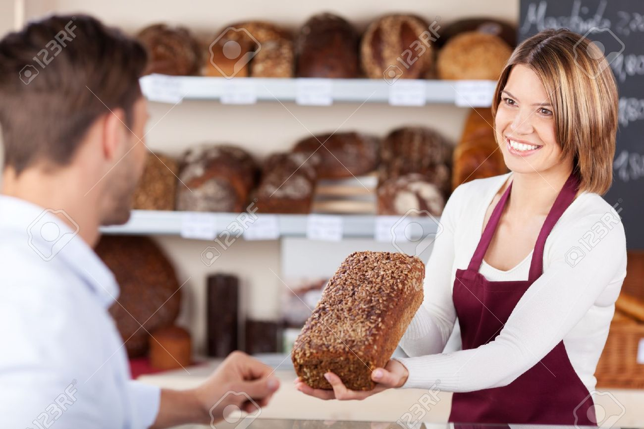 smiling friendly young bakery assistant selling b showing smiling friendly young bakery assistant selling b showing a wholewheat loaf to a male customer stock