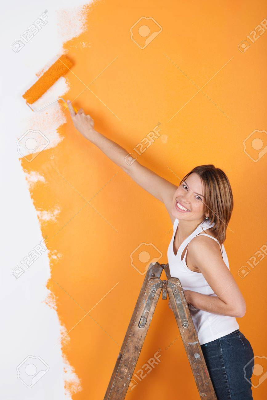 Smiling girl is painting her wall wit a roller Stock Photo - 21162114