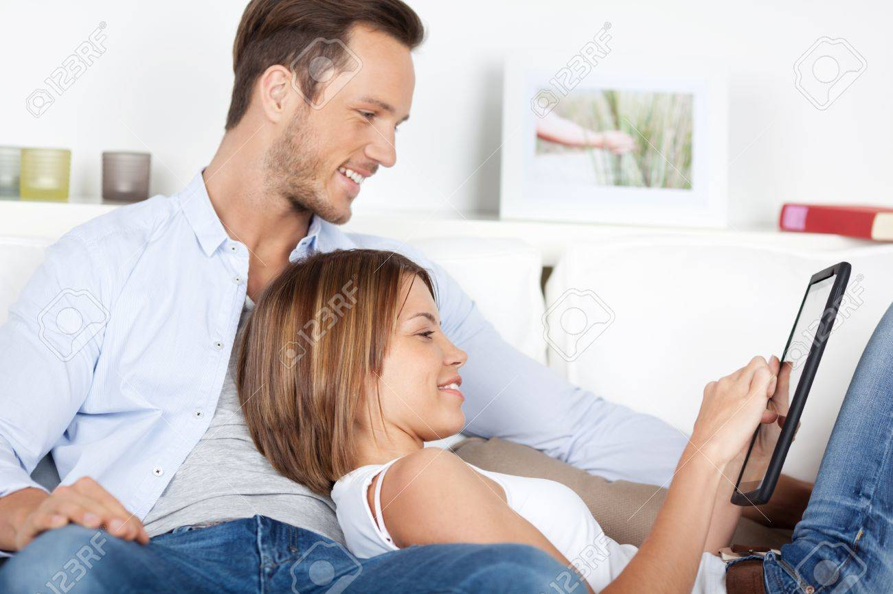 Portrait of sweet couple playing using digital tablet in living room Stock Photo - 21162446