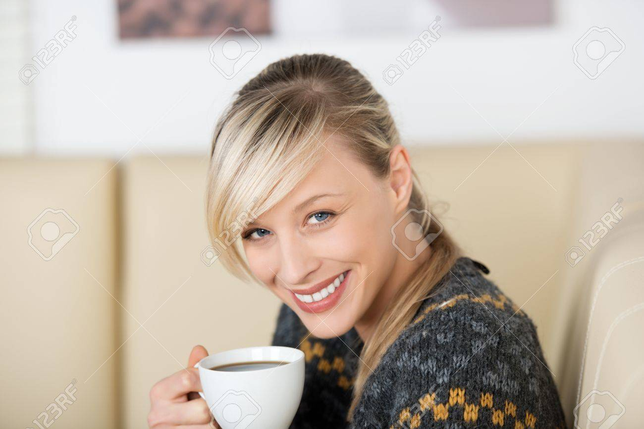 Happy blond woman drinking coffee at home Stock Photo - 21164415