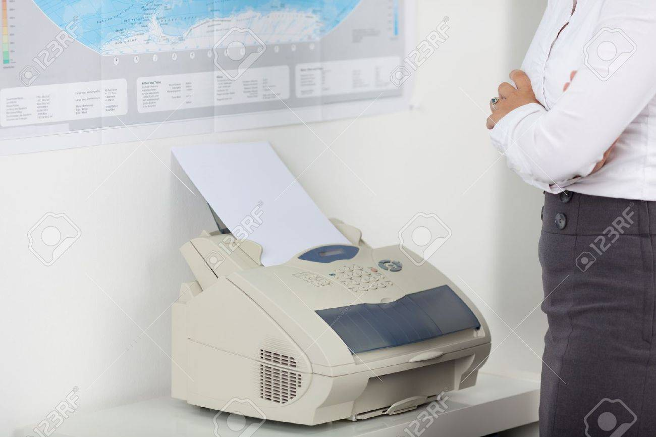 Midsection of businesswoman using fax machine in office Stock Photo - 21167607