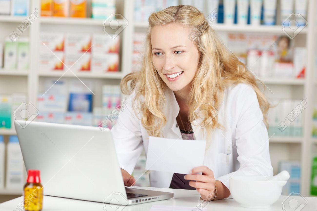 Portrait of young female pharmacist holding prescription while using laptop at pharmacy counter Stock Photo - 21170363