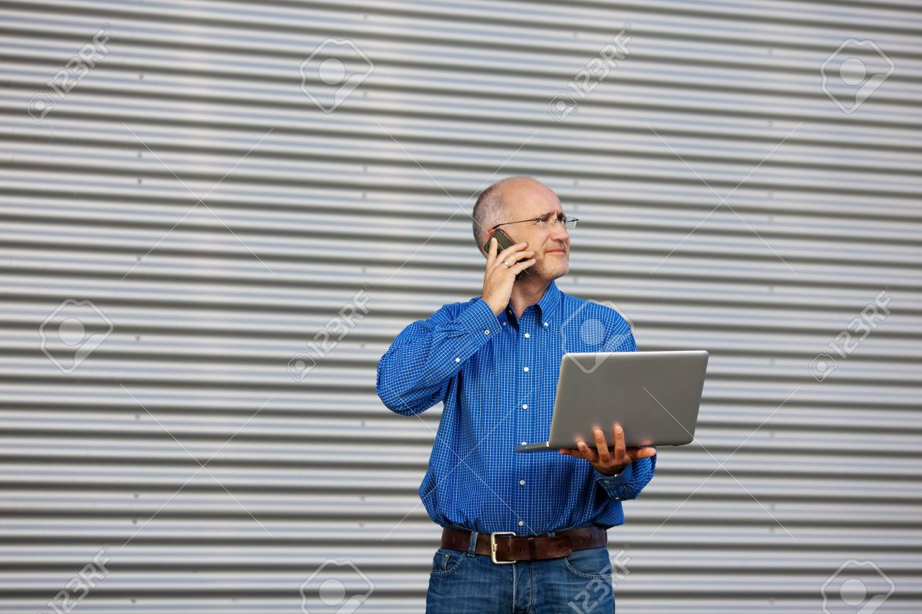 Mature businessman with laptop using cell phone while looking away against shutter Stock Photo - 21194750