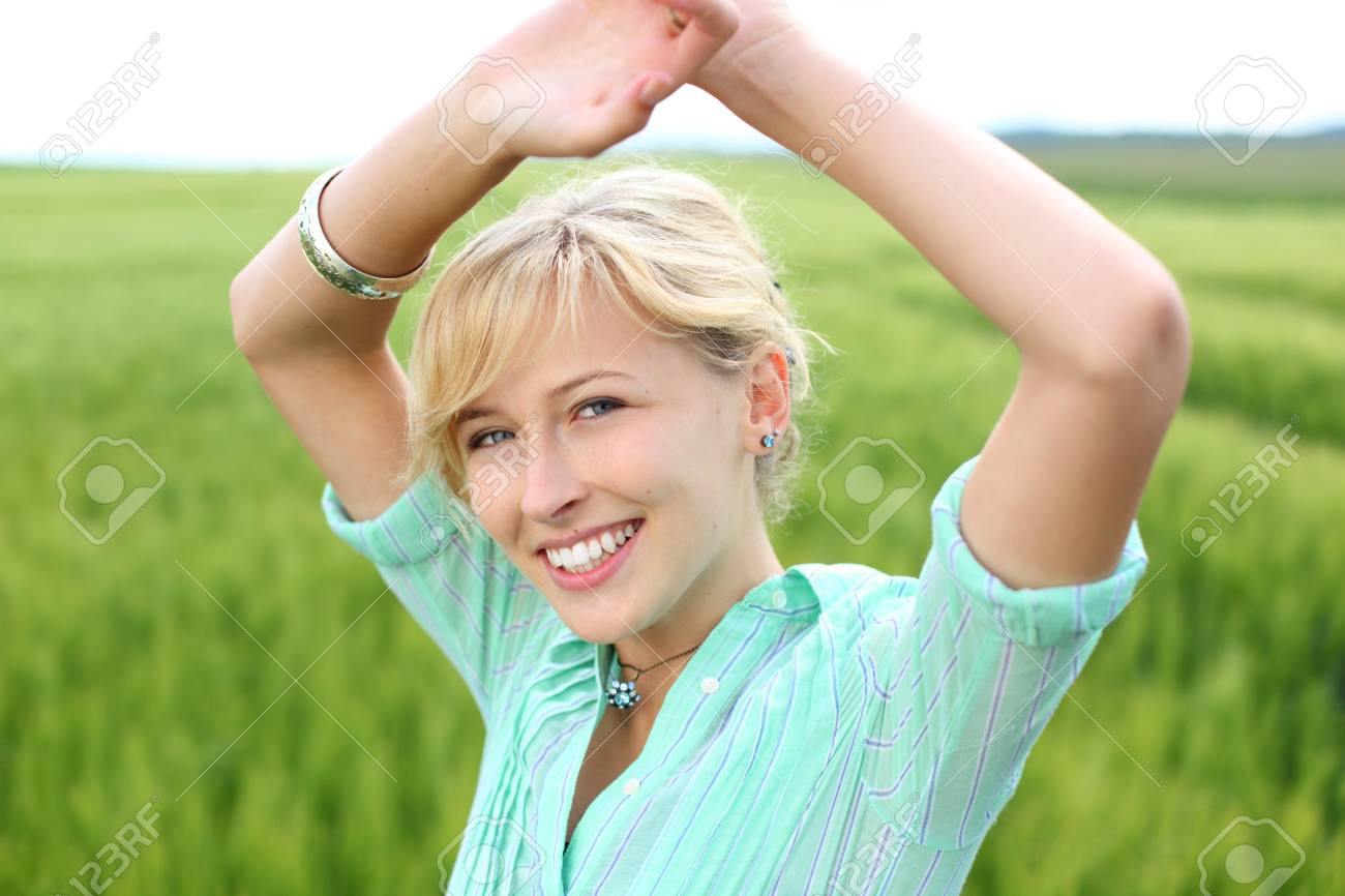 Smiling blond woman isolated on Greenfield background Stock Photo - 21195185