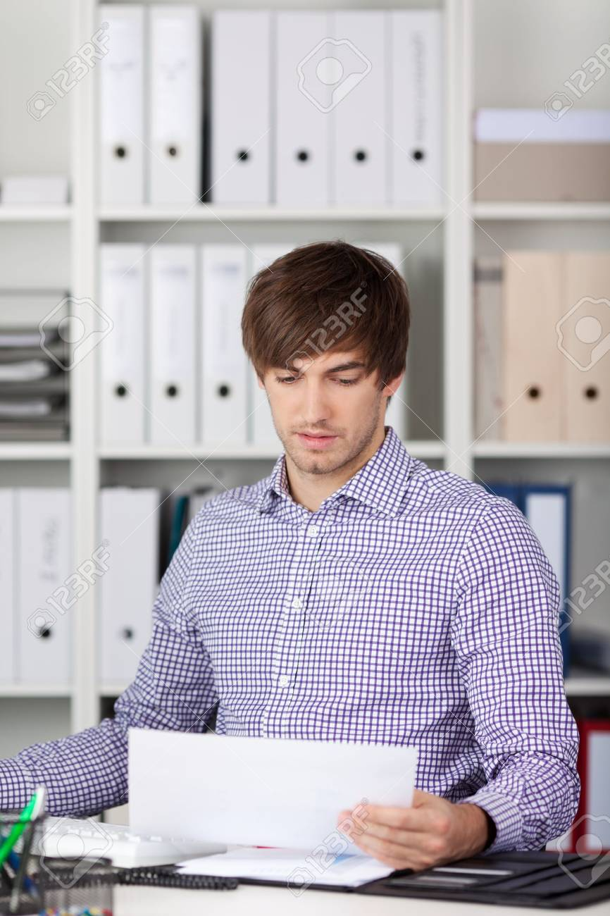 Portrait of handsome young businessman reading paper at desk in office Stock Photo - 21204113