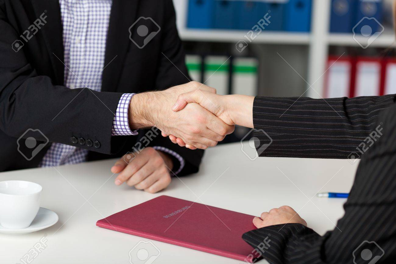 Businessman and businesswoman shaking hands at office desk Stock Photo - 21204174