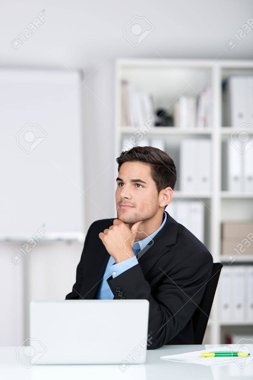 Thoughtful Businessman In The Office Sitting At His Desk Behind