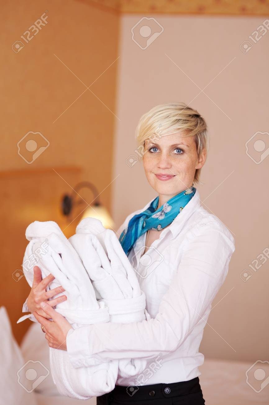 Portrait of happy female housekeeper with bathrobes Stock Photo - 21217593