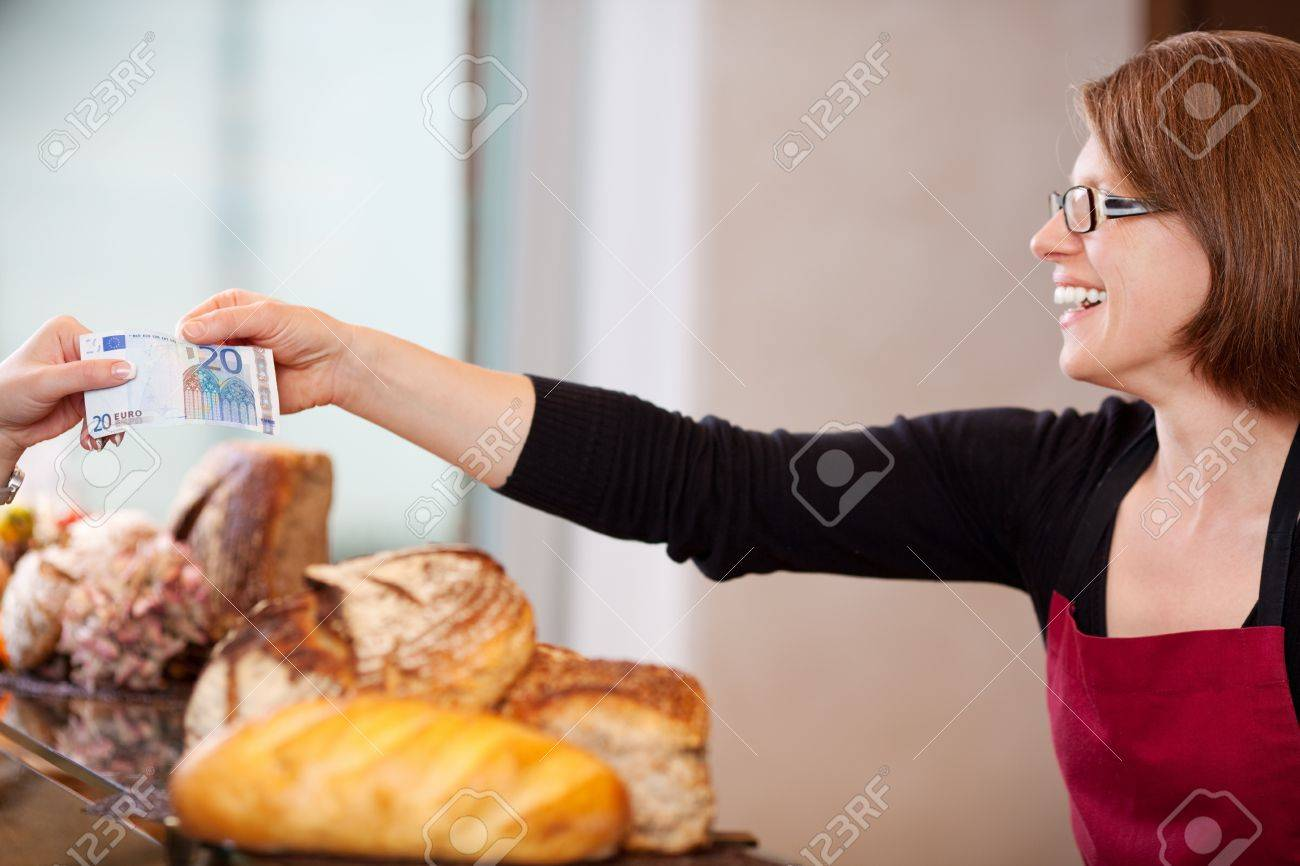 smiling saleswoman receiving 20 euro in bakery Stock Photo - 21254081
