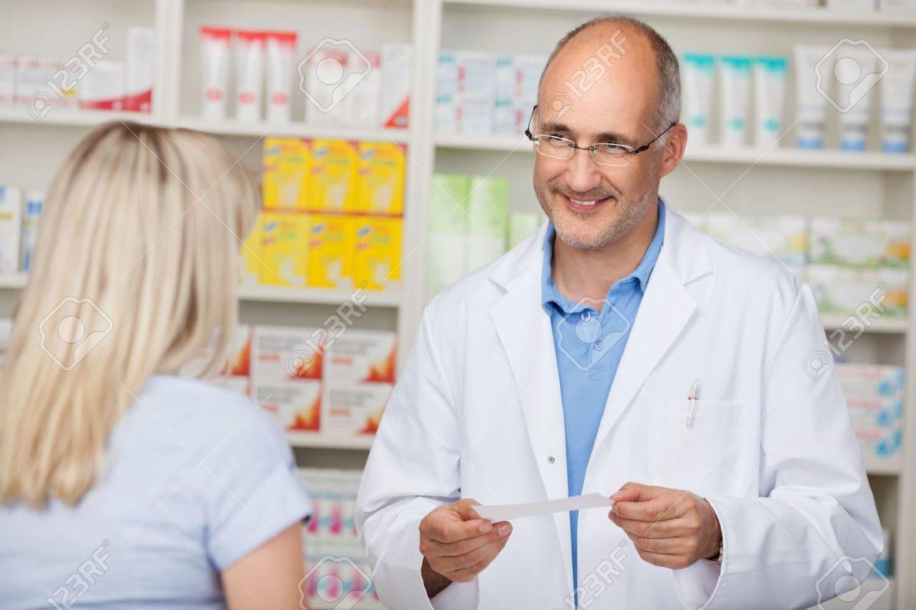 confident mature pharmacist in customer interview w stock stock photo confident mature pharmacist in customer interview w
