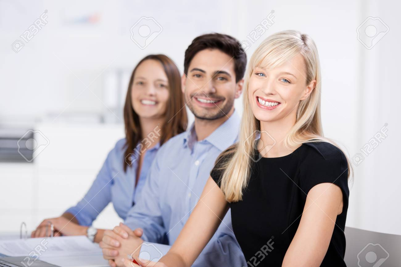Successful business team in the office seated in a receding row smiling at the camera with a beautiful blond woman in the foreground Stock Photo - 21243159