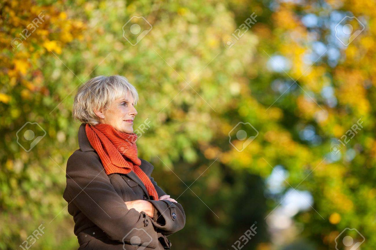 Thoughtful senior woman in jacket with arms crossed looking away in park Stock Photo - 21246815