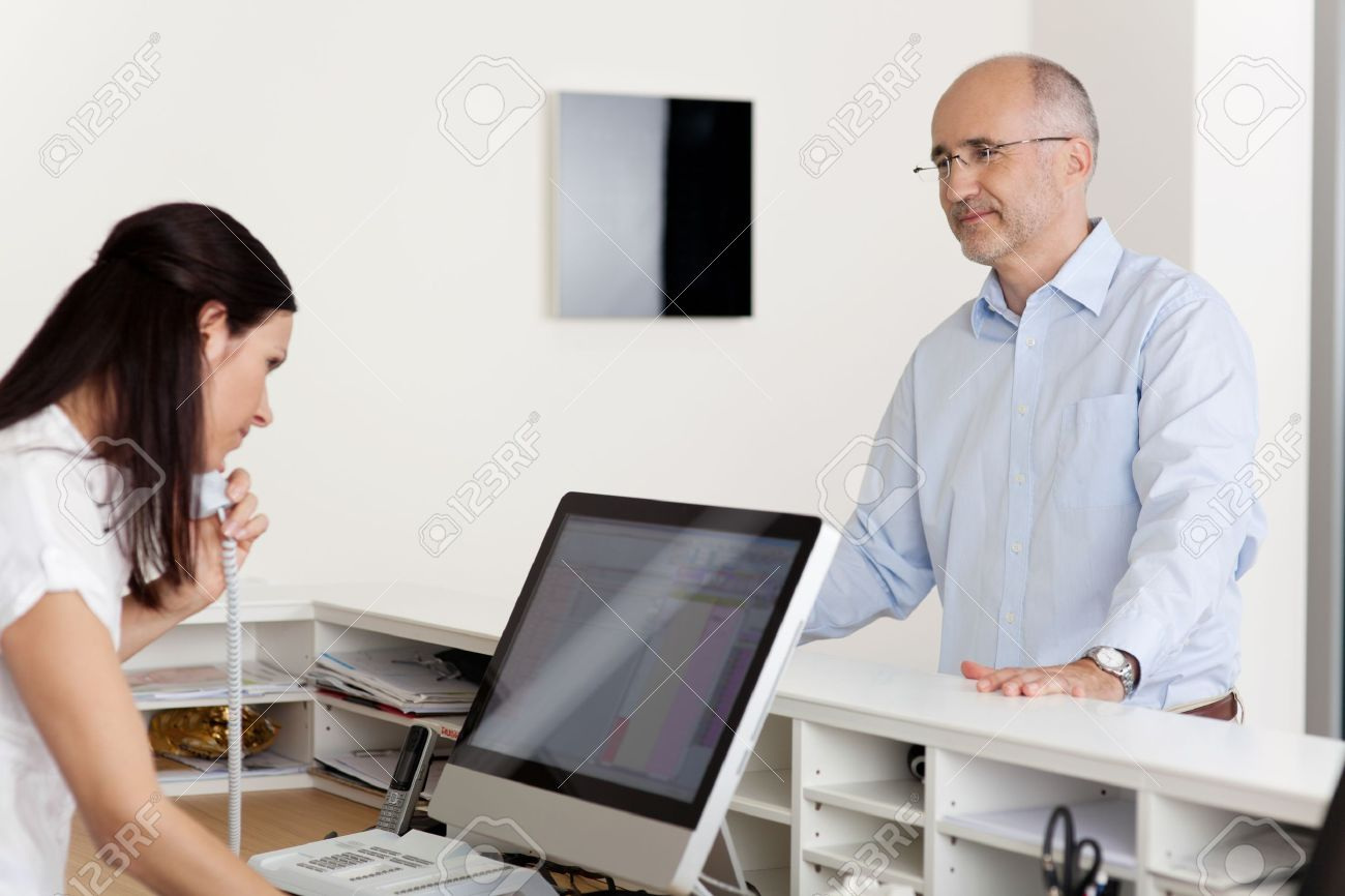 Mature male patient looking at female receptionist using landline phone and computer at reception in dentist's clinic - 21246962