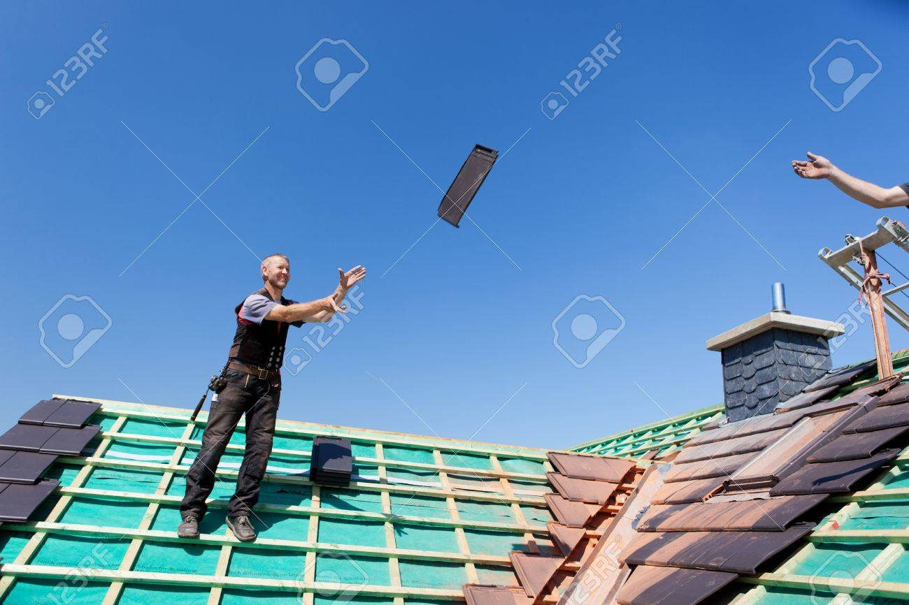 Two roofers transfer tiles across the roof by tossing them through the air Stock Photo - 21259879