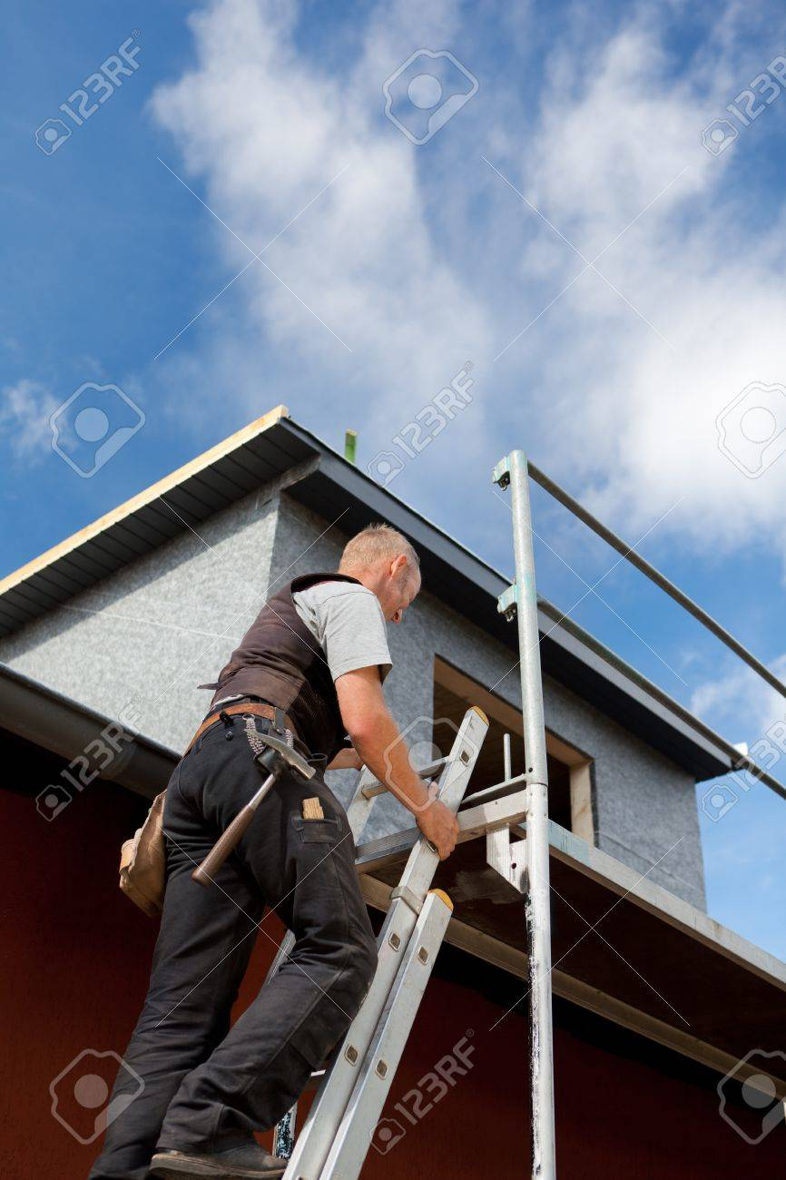 Roofer climbing a ladder into the scaffolding at the construction site Stock Photo - 21259959