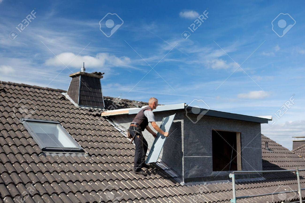 Roofer carrying a metal piece through the rooftop to the dormer wall Stock Photo - 21259960