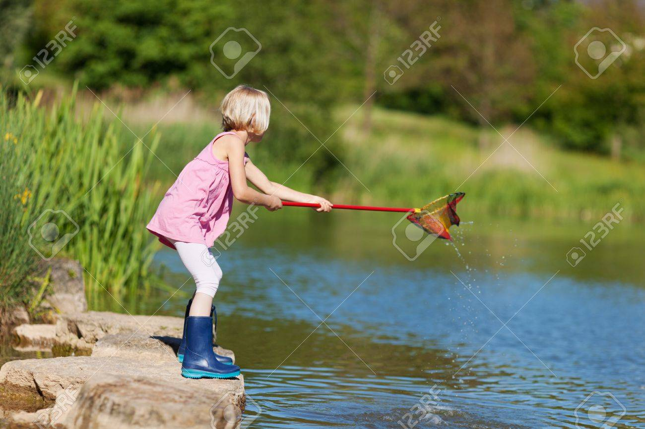 Little girl with a fishing net standing balanced on a rock at the edge of a lake in her gumboots in the summer sunshine Stock Photo - 21265347