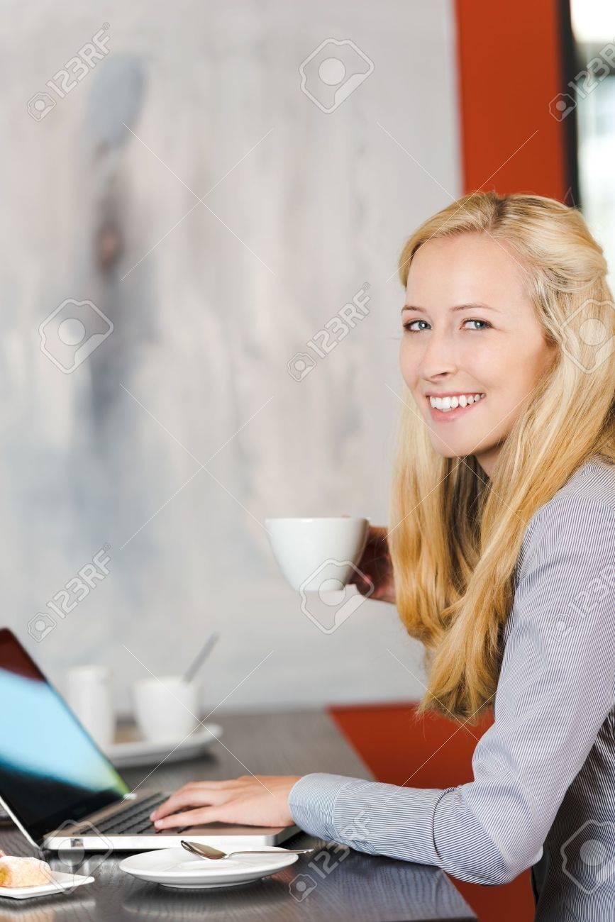 smiling blonde woman using laptop at cafe Stock Photo - 21266615