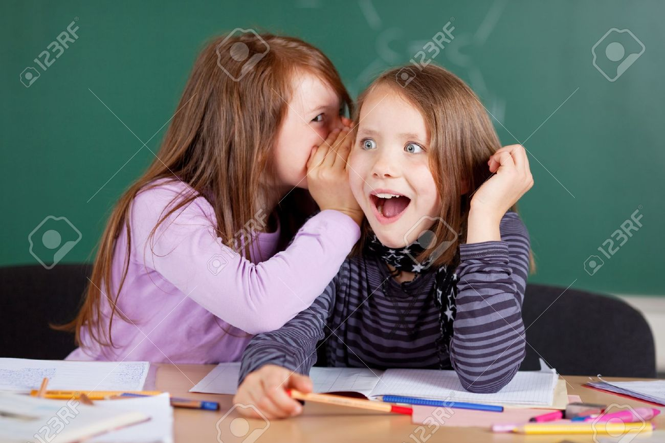 Two young girls whispering and sharing a secret during class in school - 21279299