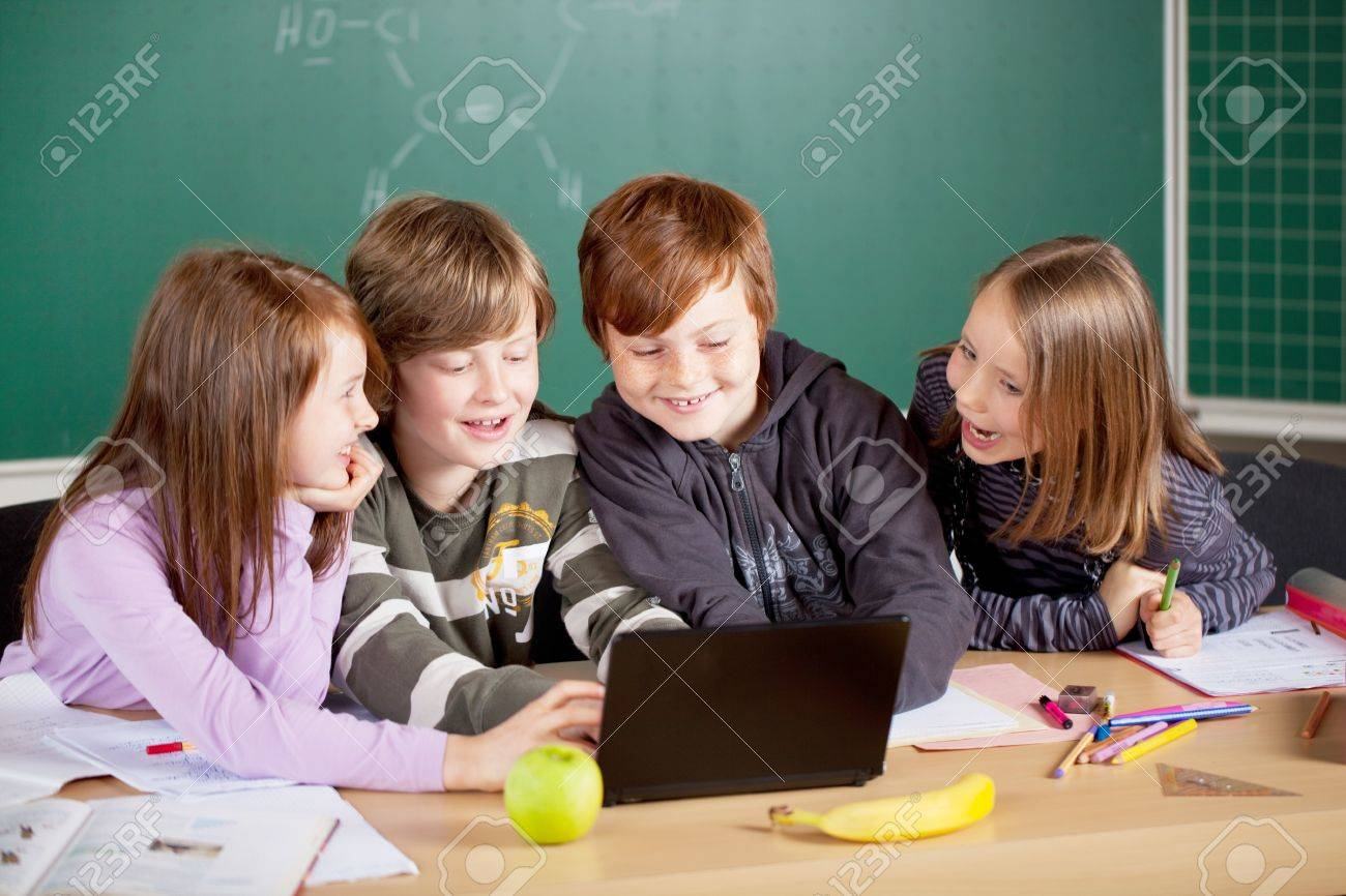 Schoolchildren working with laptop at the classroom Stock Photo - 21279459
