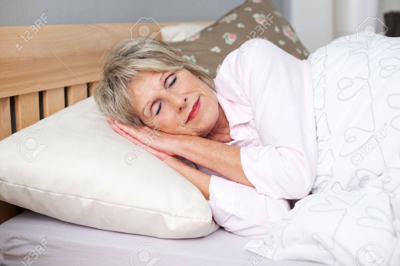 Senior woman smiling while sleeping in bed Stock Photo - 21289987