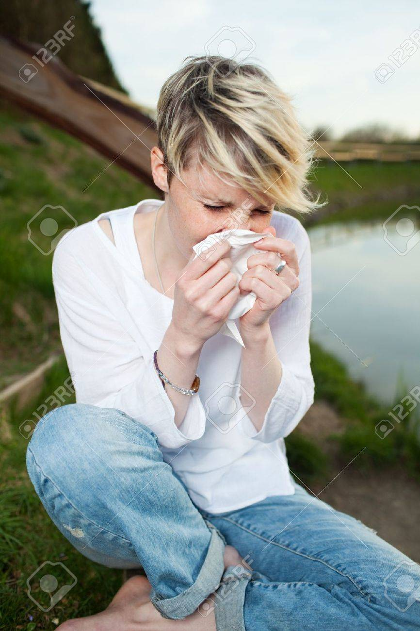 Young woman sneezing into handkerchief by the lake - 21290213