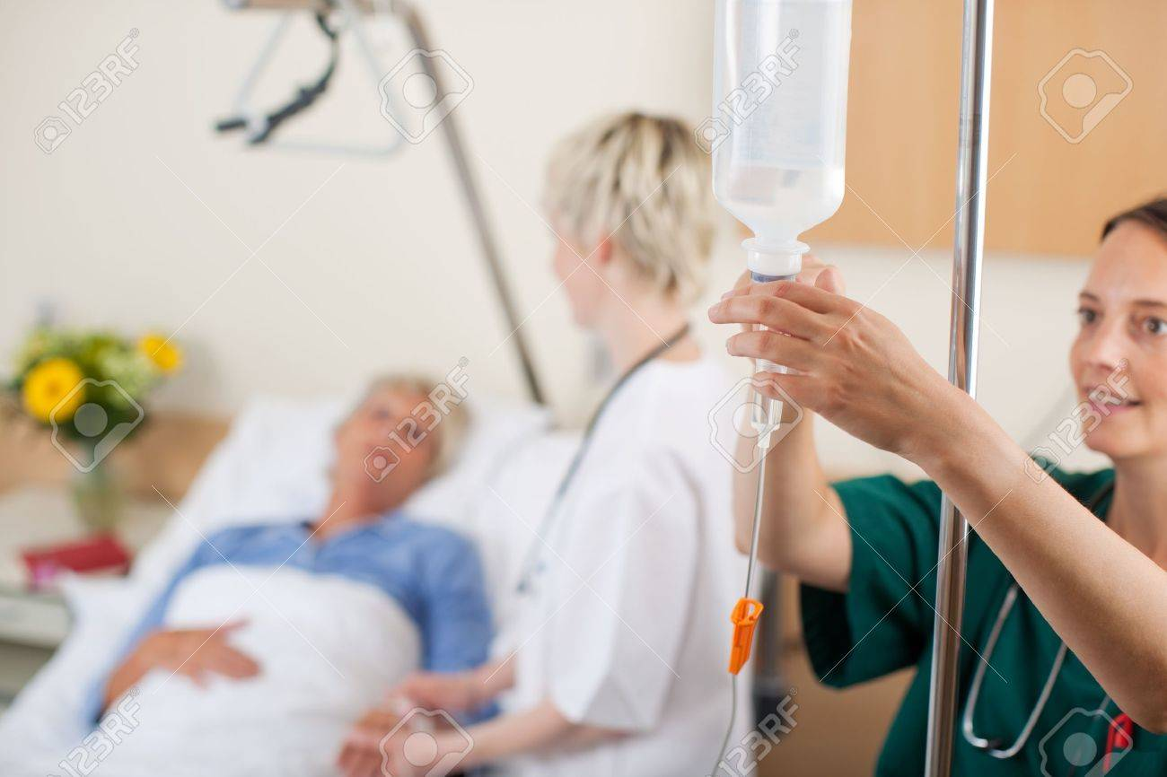Nurse adjusting infusion bottle with doctor and patient in background in hospital - 21290746