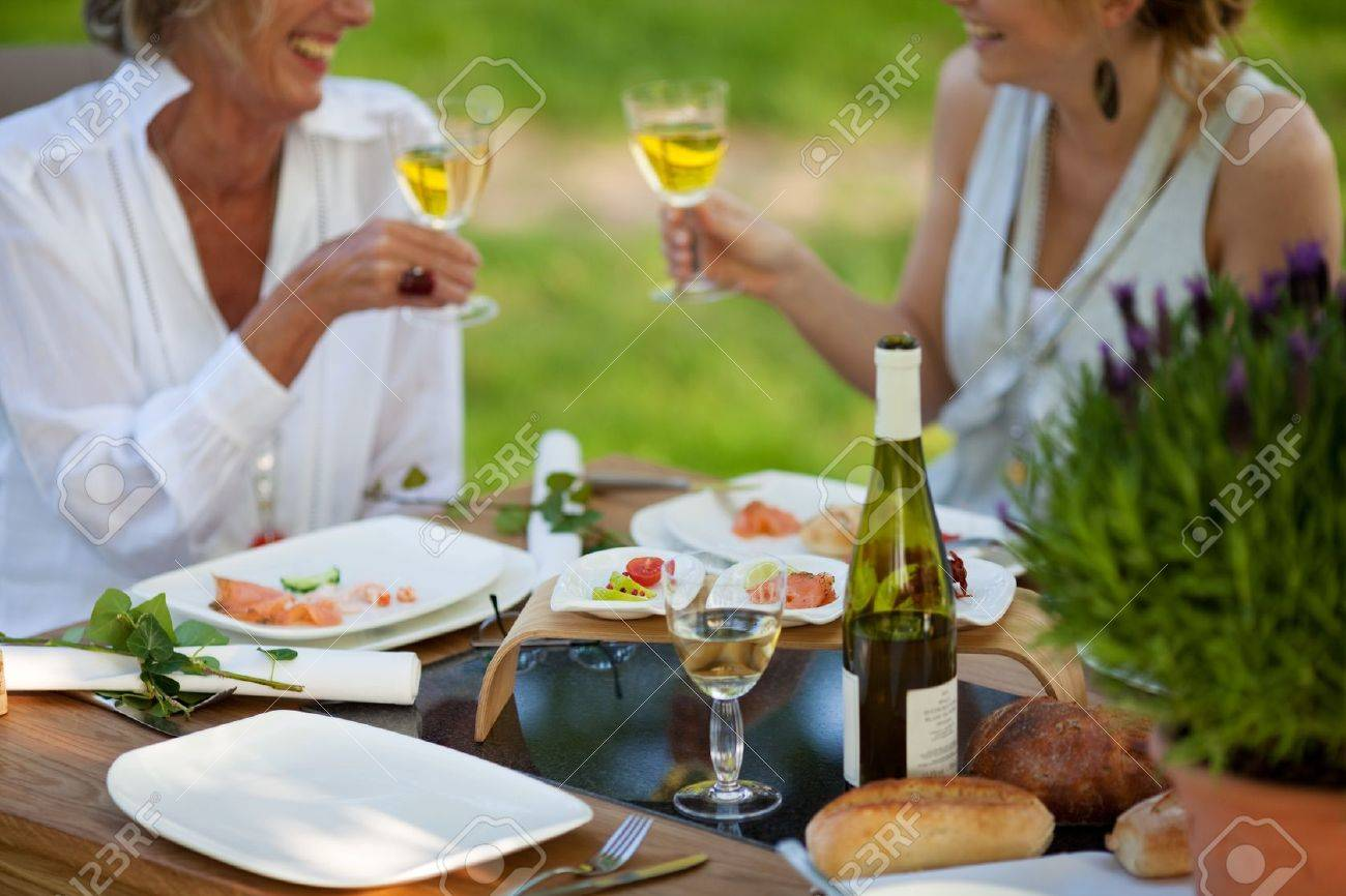 Two Women Saying Cheers At Dining Table Outdoors Stock Photo ... 8f421924c