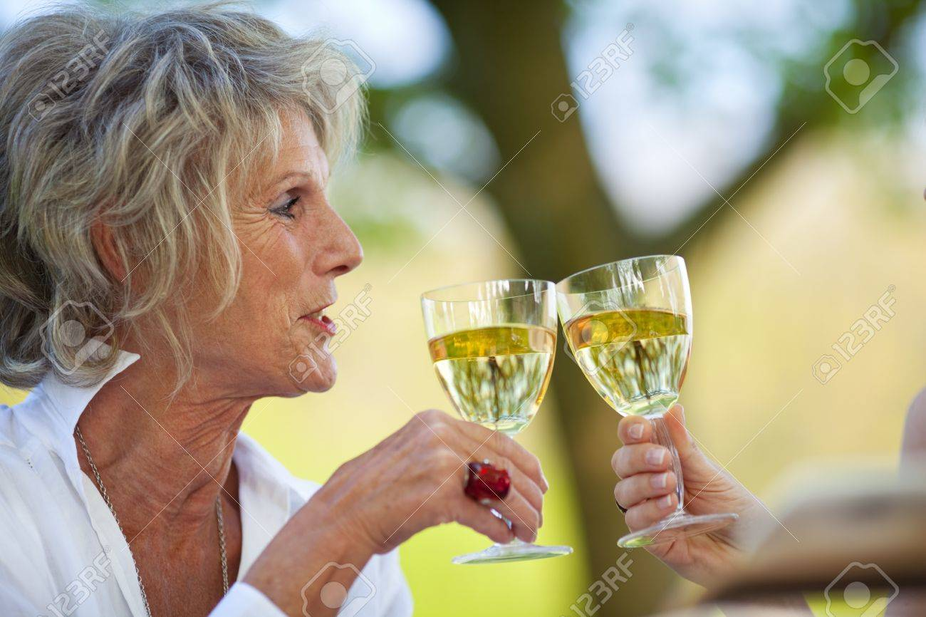 smiling elderly woman saying cheers with white wine Stock Photo - 21287166