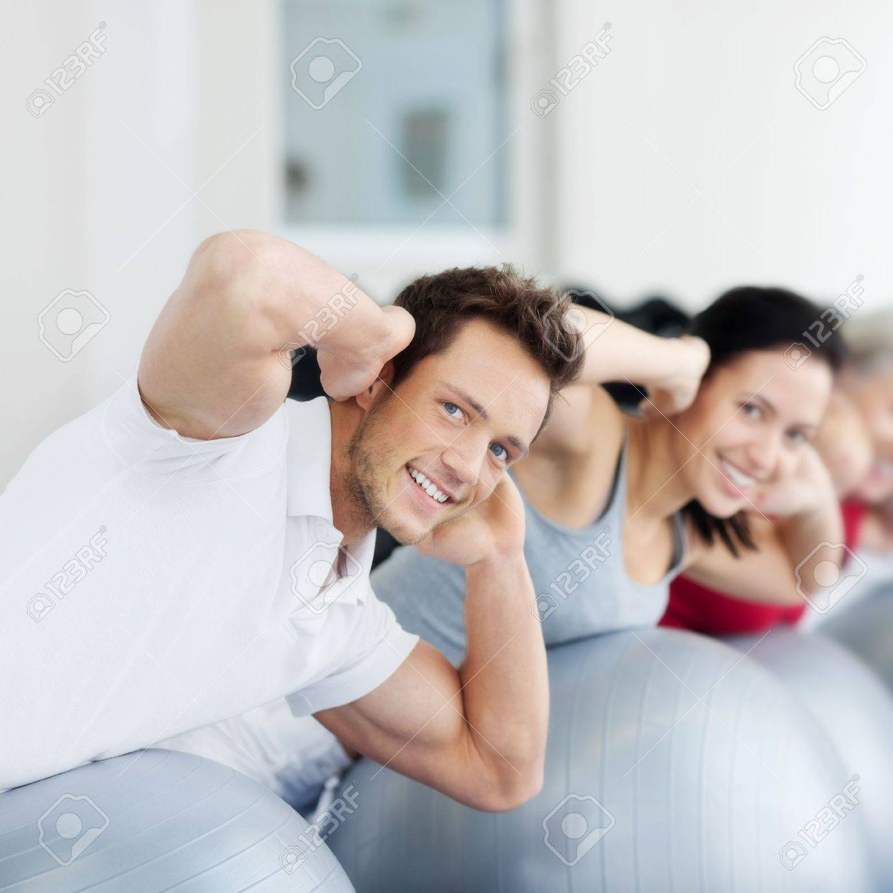 Portrait of happy group exercising on Swiss ball Stock Photo - 21315619