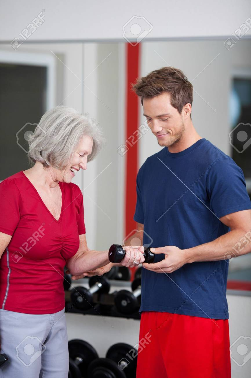 Young handsome male trainer standing with a senior woman in the gym showing her how to flex and raise her arm while holding a dumbbell weight Stock Photo - 21315653