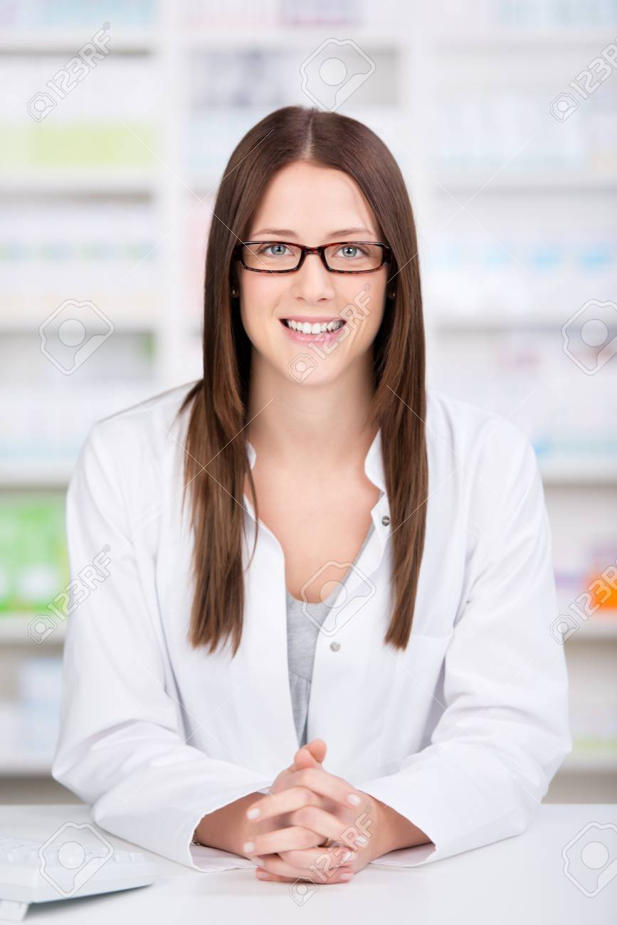 Friendly young female assistant or pharmacist standing behind the counter in the pharmacy ready to dispense medicine Stock Photo - 21341159