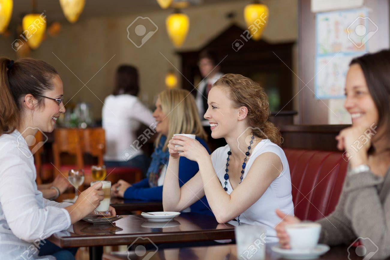 Guests enjoying coffee in a restaurant with focus to two stylish young woman sitting at a table together Stock Photo - 21375211
