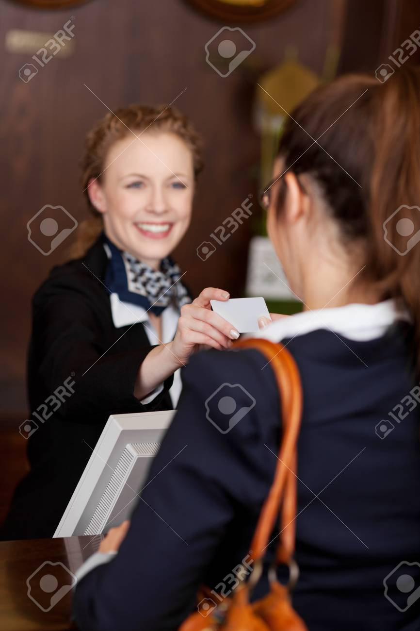 Guest receiving a business card at reception from a beautiful smiling young receptionist with focus to the card Stock Photo - 21375245