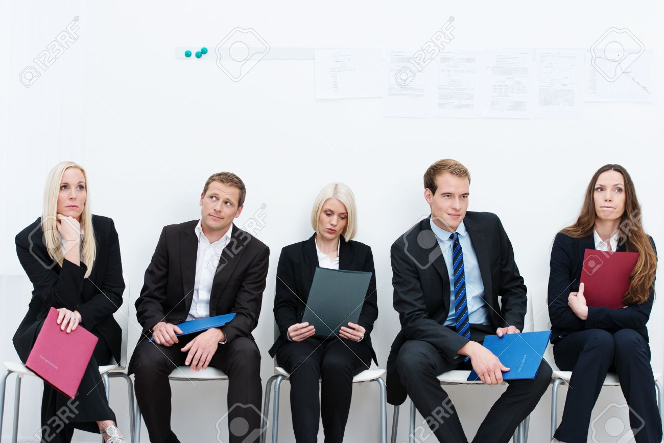 Group of applicants for a vacant post or corporate job sitting in a long line with folders containing their credentials carefully ignoring each other Stock Photo - 22082519