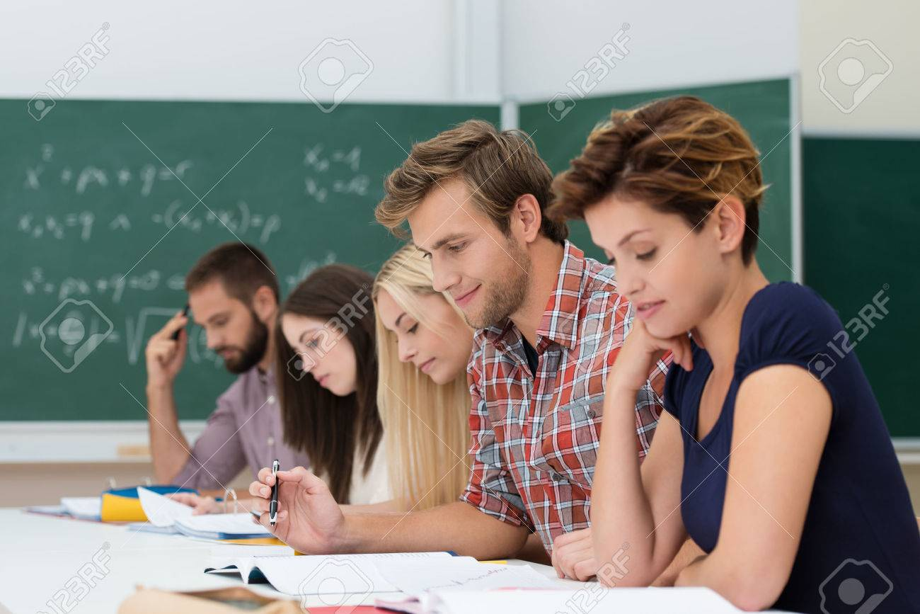 Mixed group of Caucasian determinated students studyng, looking at their notes at their desks in the class, with a chalkboard in the background Stock Photo - 22250105