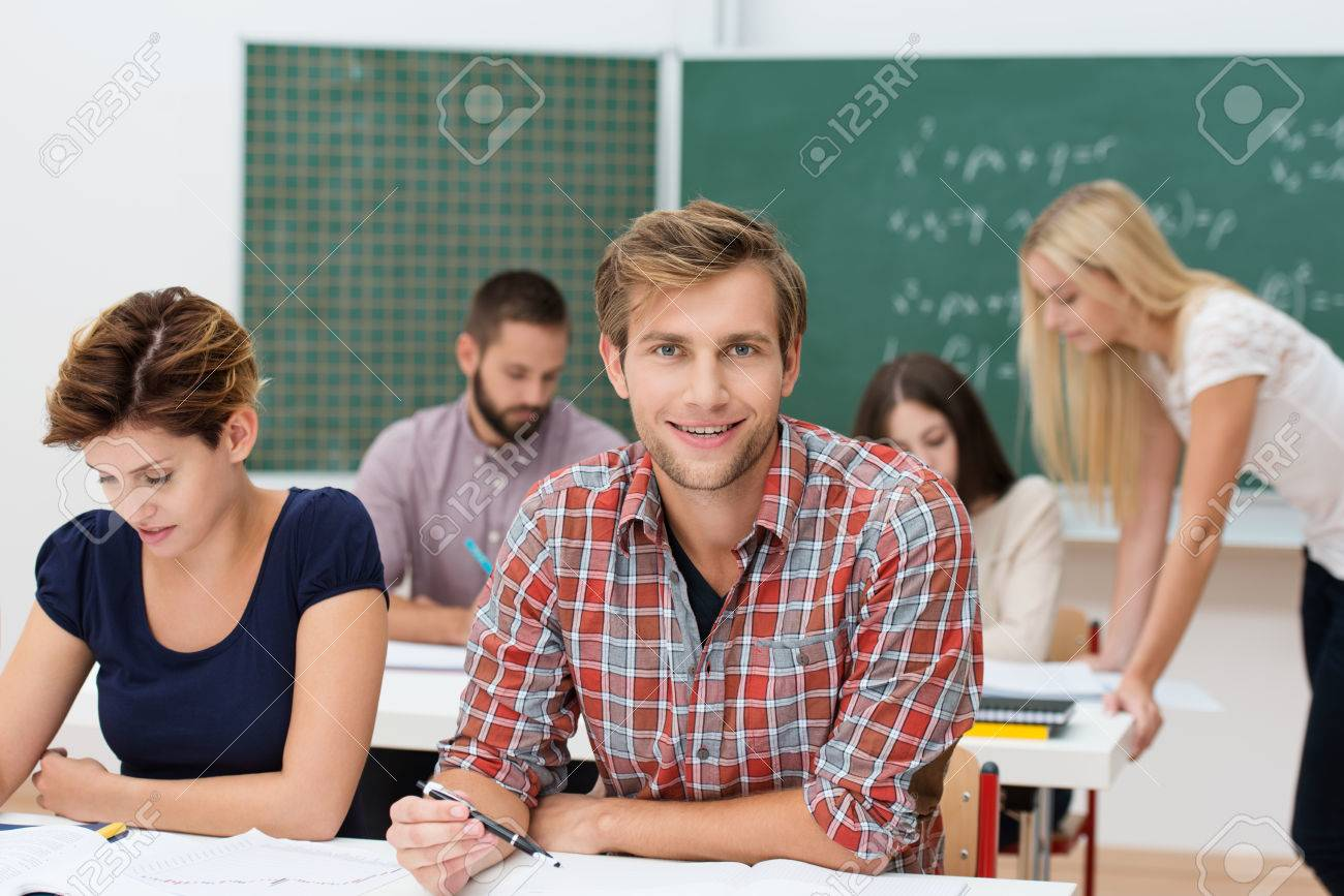 Smiling attractive unshaven young man at college or university sitting at his desk in the classroom surrounded by other hardworking students Stock Photo - 22250155