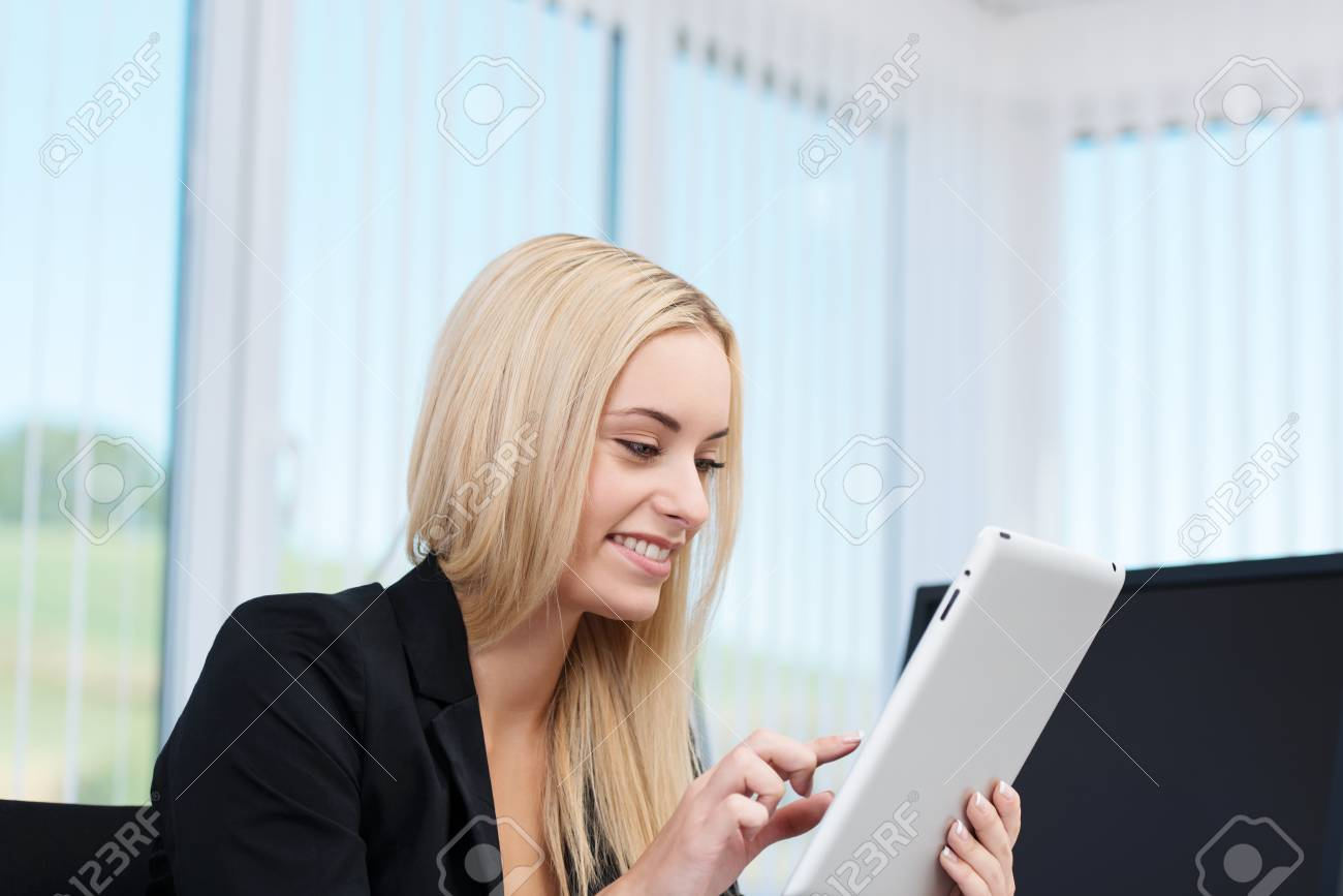 Young businesswoman sitting in her office working on a tablet computer navigating with her finger on the touchscreen Stock Photo - 22345817