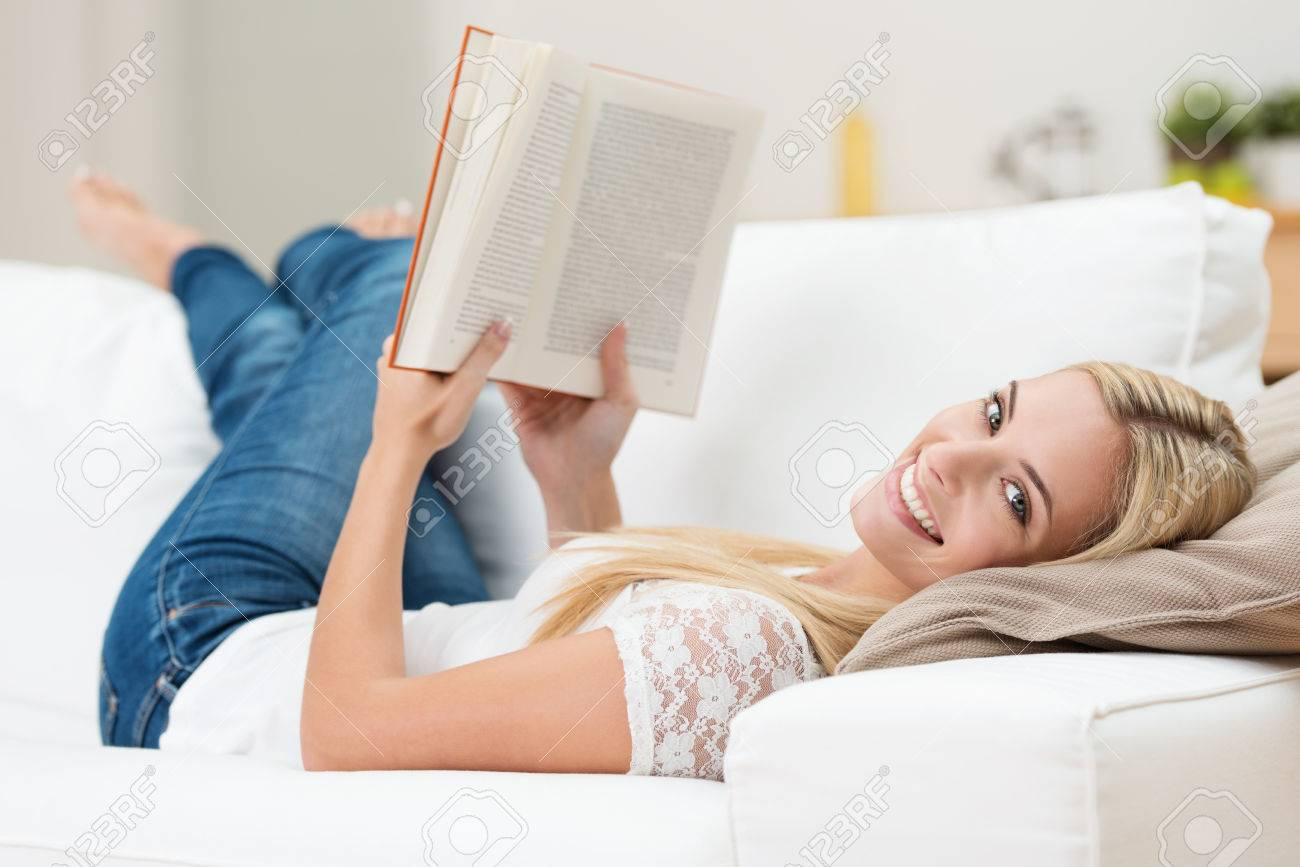 beautiful relaxing furniture. Beautiful woman reading on a sofa relaxing with her bare feet over the arm  of furniture Woman Reading On A Sofa Relaxing With Her Bare Feet